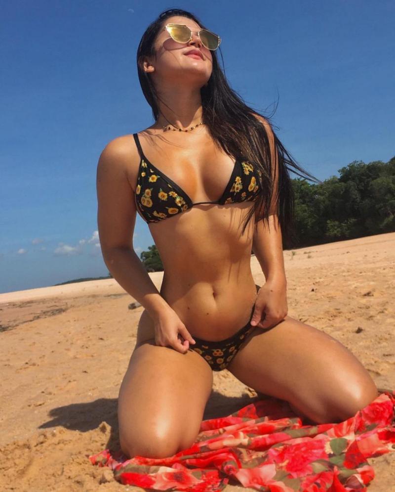 De biquíni e cinturinha, Janny Canafistulla posa de joelhos em praia de Santarém